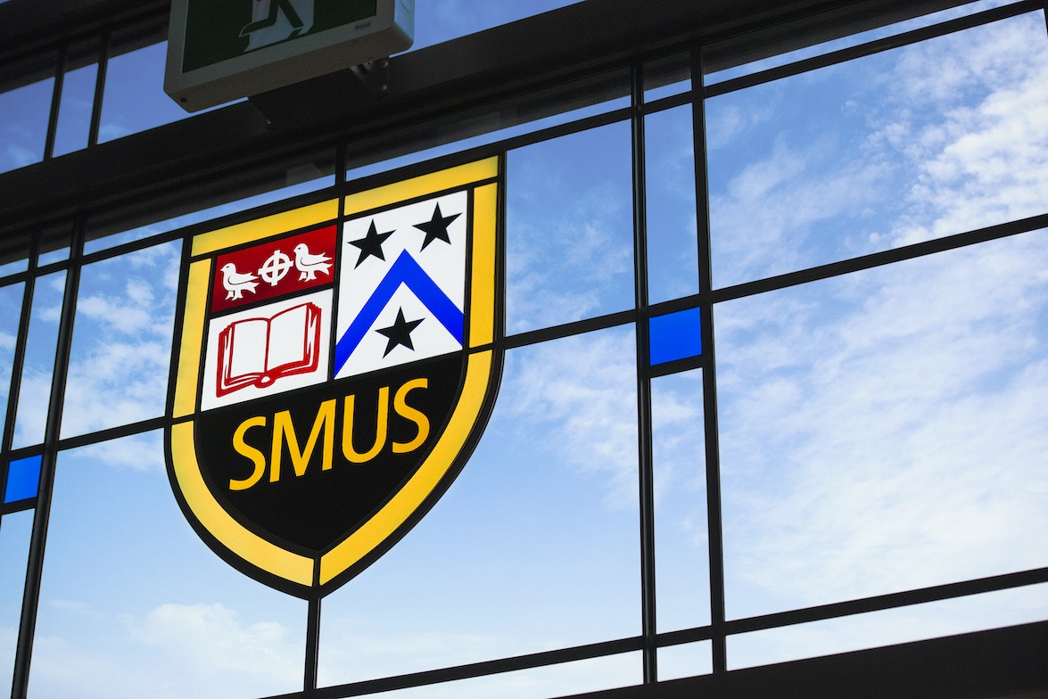 SMUS crest visible through stained glass