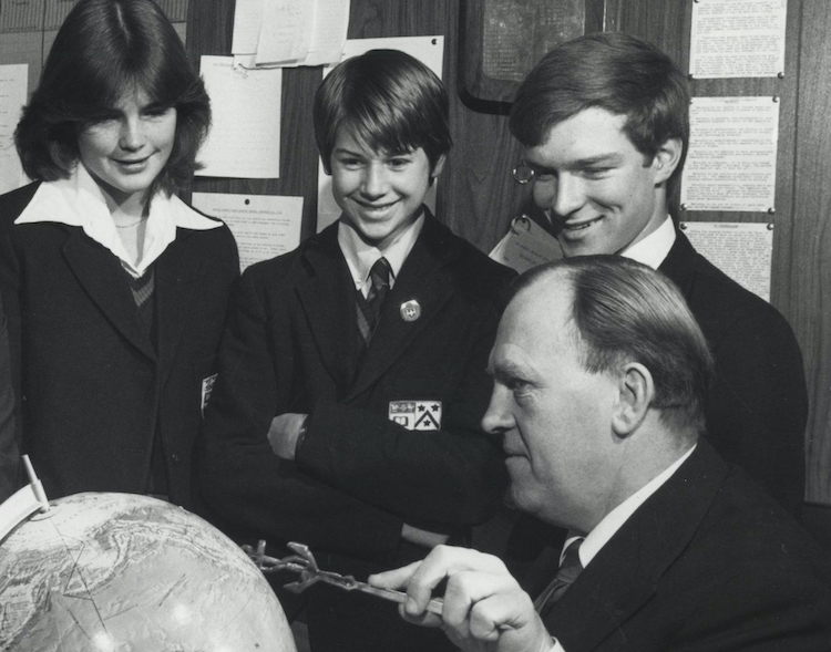 Archival photo of students with teacher and globe.
